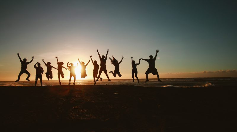 Image of adults jumping with sun in background